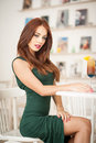 Fashionable Attractive Young Woman In Green Dress Sitting In Restaurant Royalty Free Stock Images - 47434729