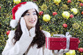 Girl With A Gift Near Christmas Tree Stock Images - 47457394