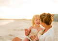 Laughing Mother And Baby Girl Sitting On Beach Stock Photos - 47531433
