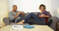 Black Couple Using Electronic Devices On Couch Royalty Free Stock Images - 47558109