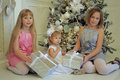 Three Girls Sisters Sitting At The Christmas Tree Stock Image - 47574751