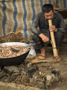 A Man Is Smoking A Large Pipe Behind A Large Pan With Meat At Bac Ha Morning Market Stock Photo - 47637140