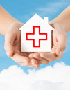 Hands Holding Paper House With Red Cross Stock Photography - 47639302