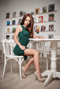 Fashionable Attractive Young Woman In Green Dress Sitting In Restaurant. Beautiful Redhead Posing In Elegant Scenery With Juice Stock Photo - 47646160