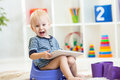 Child Sitting On Chamber Pot Playing Tablet Pc Royalty Free Stock Photography - 47683737