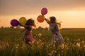 Women And Girl Jumping With Balloons Outdoor Royalty Free Stock Photography - 47885277