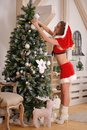 Sexy Santa Claus Girl Putting Christmas Ornaments On The Tree Royalty Free Stock Photos - 48145078
