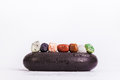 Row Of Chakra Crystals On Hot Massage Black Stones Royalty Free Stock Images - 48564029