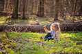 Cute Child Girl Sitting In Green Leaves In Early Spring Forest Royalty Free Stock Image - 48840706