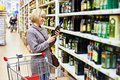 Woman Reading Label On Bottle Of Olive Oil In Store Royalty Free Stock Image - 48869506