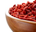 Wooden Bowl Full Of Dried Goji Berries On The White Table Stock Images - 49049904
