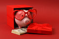 Piggy Bank In Love With Red Heart Sunglasses Standing In Gift Box With Ribbon And With Stack Of Money American Hundred Dollar Bill Royalty Free Stock Photos - 49067848
