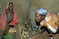 Breeding Chicks By Ugandan Woman With Son Stock Image - 49157471