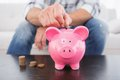 A Man Putting Coins In Piggy Bank Stock Photo - 49225430