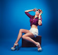 Beautiful Pin-up Girl Posing With Vintage Suitcase Against Blue Stock Photo - 49257610