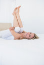 Smiling Blonde Woman With Legs Raised In Bed Stock Image - 49269081