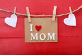 Mothers Day Message With Clothespins Over Red Wooden Board Royalty Free Stock Images - 49337759