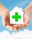 Hands Holding Paper House With Green Cross Stock Image - 49425901