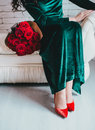 Beautiful Woman In A Green Dress And Red Shoes With Red Roses Royalty Free Stock Images - 49517569