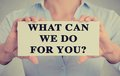 Businesswoman Hands Holding Sign With What Can We Do For You Stock Photo - 49553200