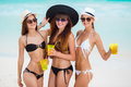 Three Girls In Hats Drinking Juice Near The Sea Stock Photography - 49631622