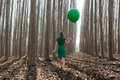 Beautiful Blonde Girl, Dressed In Green, Walking Into The Forest Stock Image - 49643071