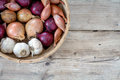 Onions And Garlic In A Basket On Wooden Background Stock Photos - 49791023