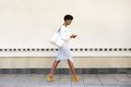 Young Woman Walking And Sending Text Message On Cell Phone Royalty Free Stock Photography - 49841137