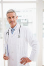 Doctor Holding Clipboard Smiling At Camera Royalty Free Stock Photography - 49886117