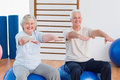 Senior Couple With Arms Raised Sitting On Exercise Ball Royalty Free Stock Photo - 49894605