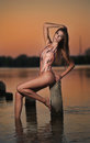 Beautiful Girl In Swimsuit Posing Provocatively During Sunset At River Shore. Attractive Slim Brunette Woman Sitting On Pillar Stock Photos - 49918413