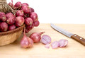 Close Up Red Onion Or Shallots In Wooden Basket With Sliced Onion On Wooden Chopping Block Stock Images - 49952474