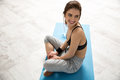 Happy Sports Woman Sitting On The Yoga Mat Royalty Free Stock Images - 49983189