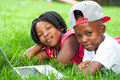 African Kids Laying On Grass With Laptop. Royalty Free Stock Photos - 50034928