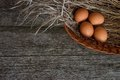 Chicken Eggs In Straw Basket On Rustic Wooden Background Stock Photo - 50077770