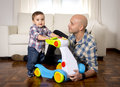 Young Father And Little Son Walking With Baby Walker Taking His First Brave Steps Royalty Free Stock Image - 50157546