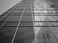A View From The Sidewalk In Front Of A Glass Sky Scraper Shows A Reflection Of The Grace Building. Royalty Free Stock Photo - 50183825
