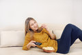 Cute Smilling Young Woman Watching TV And Relaxing On Sofa At Ho Royalty Free Stock Photography - 50364237