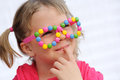 Portrait Of Cute Little Girl Wearing Funny Glasses, Decorated With Colorful Smarties, Candies Royalty Free Stock Photos - 50392538