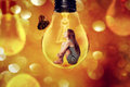 Lonely Woman Sitting Inside Light Bulb Looking At Butterfly Royalty Free Stock Image - 50463696