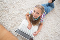 Cute Girl Using Laptop While Lying On Rug Stock Photography - 50492562