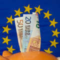 Piggy Bank With Euro Notes, EU Flag In The Background Royalty Free Stock Photo - 50500735