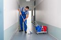 Male Worker With Broom Cleaning Office Corridor Royalty Free Stock Photos - 50572148