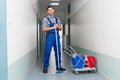 Happy Male Worker With Broom Cleaning Office Corridor Royalty Free Stock Photography - 50572197
