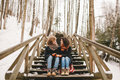 Young Couple Sitting On Wooden Stairs Outdoors In Winter Royalty Free Stock Photography - 50573907