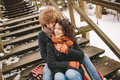 Young Couple Sitting On Wooden Stairs Outdoors In Winter Royalty Free Stock Photos - 50574118