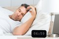 Man On Bed With Clock On Nightstand Stock Images - 50584154