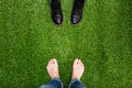 Mens Feet Resting On Green Grass Standing Opposite Boots Stock Photo - 50614460