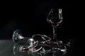 Red Wine In Broken Glass Cups Spilled On The Glass Table Isolated On Black Stock Images - 50742654