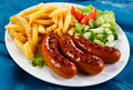 Grilled Sausages And French Fries Royalty Free Stock Image - 50898046
